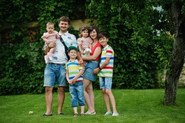 Mooie grote familie met jonge ouders en vier kinderen staan in groen gras op de binnenplaats.