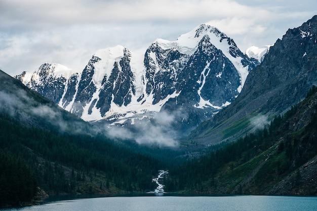 Mooie grote gletsjer, rotsachtige besneeuwde bergen, naaldbos op heuvels, bergmeer en highland creek onder bewolkte hemel. sfeervol alpenlandschap met lage bewolking op hoge steile hellingen in het bos.