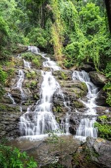 Mooie grote waterval die tussen rotsen in een donkergroen bos stroomt.