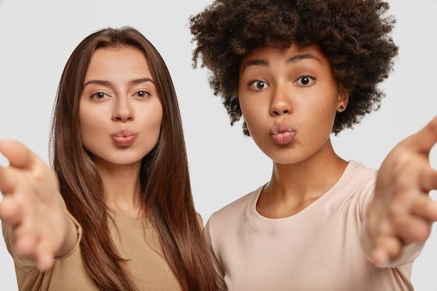 Mooie halfbloedvrouwen pruilen hun lippen, strekken hun handen uit om iemand te omhelzen, uiten hun goede gevoel, poseren samen tegen een witte muur. interraciale vriendinnen binnen.