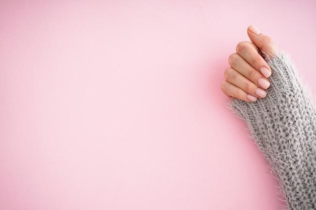 Mooie hand van een jong meisje met mooie manicure op een roze achtergrond. plat leggen, plaats voor tekst. winterverzorging, huid, spa concept