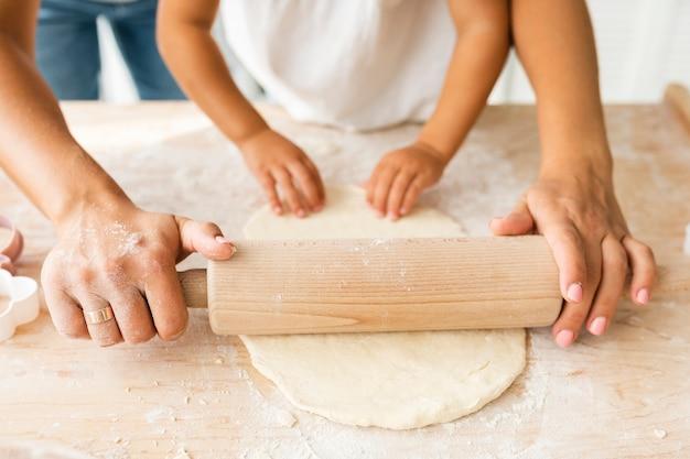 Mooie handen die keukenrol op deeg gebruiken