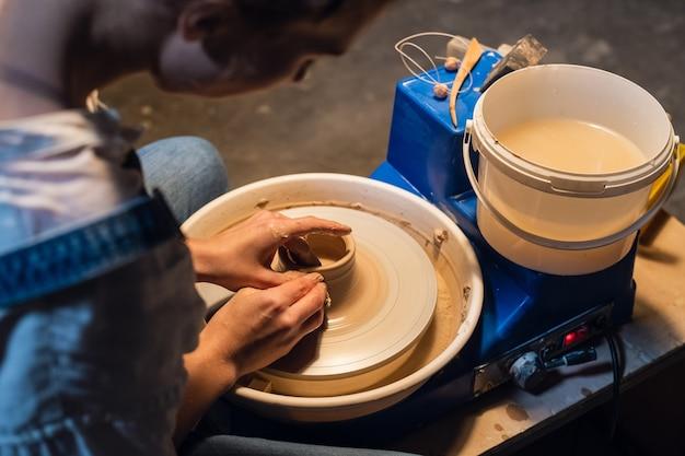 Mooie handen van een jong meisje, gekleurd met klei bij het modelleren van een pot op een pottenbakkersschijf in de werkplaats.