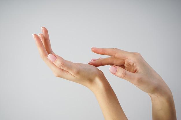 Mooie handen van een jong meisje met mooie manicure op een grijze achtergrond, spa en manicure concept.