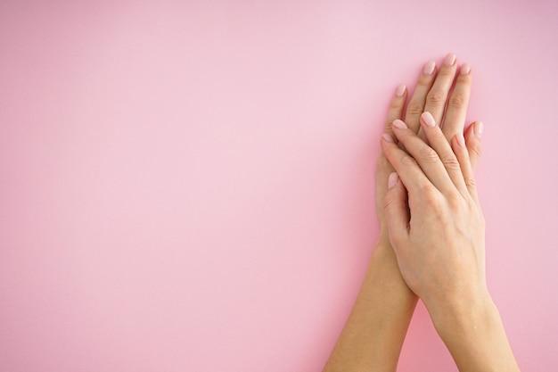 Mooie handen van een jong meisje met mooie manicure op een roze achtergrond, plat leggen, plaats voor tekst.