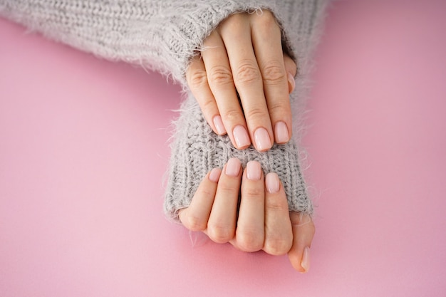 Mooie handen van een jong meisje met mooie manicure op een roze achtergrond, plat leggen. winterverzorging, huid, spa concept.