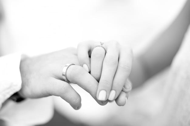 Mooie handen van paar in huwelijksceremonie met oceaanachtergrond.