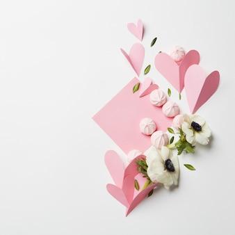 Mooie handgemaakte ansichtkaart op witte achtergrond met schuimgebakjes, roze hart en bloemen