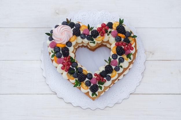 Mooie hartvormige cake met verse bessen voor valentijnsdag op witte houten tafel