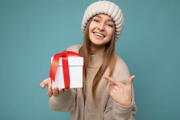 Mooie heerlijke gelukkige glimlachende donkerblonde jonge vrouw die over blauwe muur wordt geïsoleerd als achtergrond