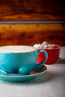 Mooie heerlijke latte-kunst, blauwe koffiekop met bruine suiker op houten achtergrond.