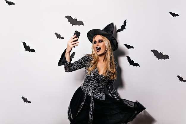 Mooie heks in fonkelingsjasje die pret in halloween hebben. boze tovenaar lachen met telefoon voor selfie.