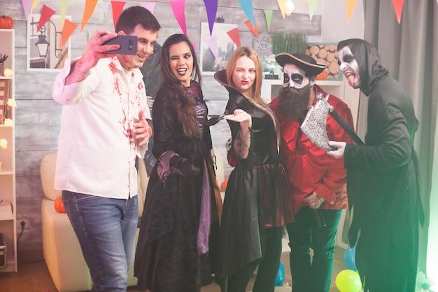 Mooie heks knipoogt terwijl de zombie een selfie neemt op halloween-feest. spookachtige kostuums.