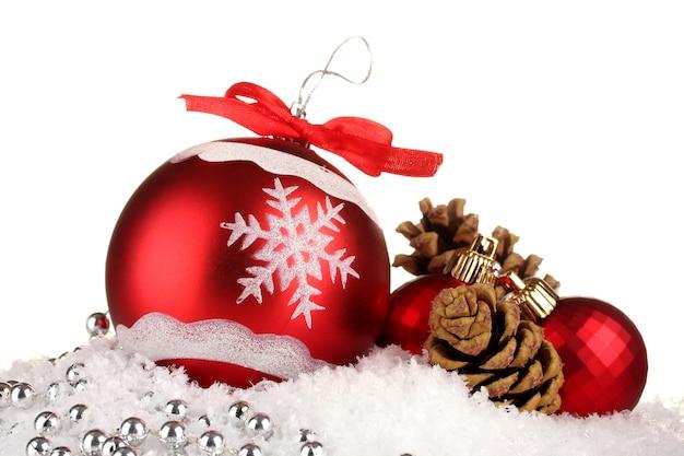 Mooie heldere kerstballen op sneeuw, geïsoleerd op wit