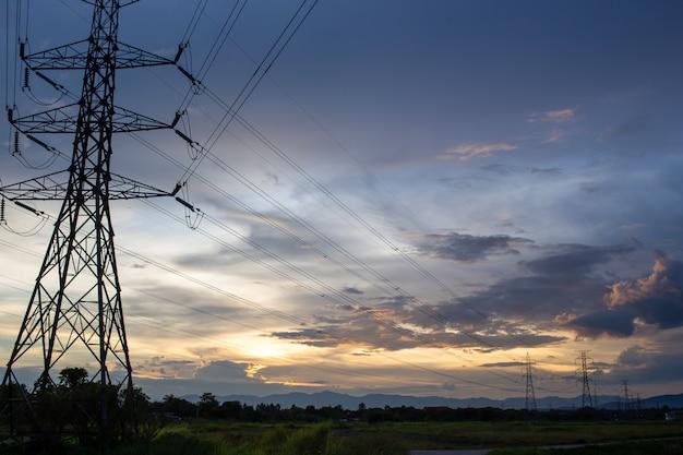 Mooie hemel in de avond en elektriciteitspalen met hoog voltage