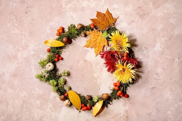 Mooie herfst botanische krans samenstelling creatieve lay-out met bloemen, mos en gele herfstbladeren over beige betonnen achtergrond. plat leggen, kopie ruimte