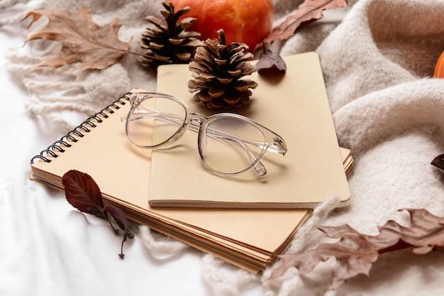 Mooie herfst compositie met notebooks en brillen op bed