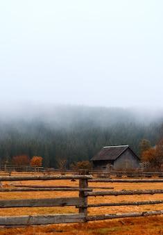 Mooie herfst landschap van een houten huis in de bergen met mistig bos