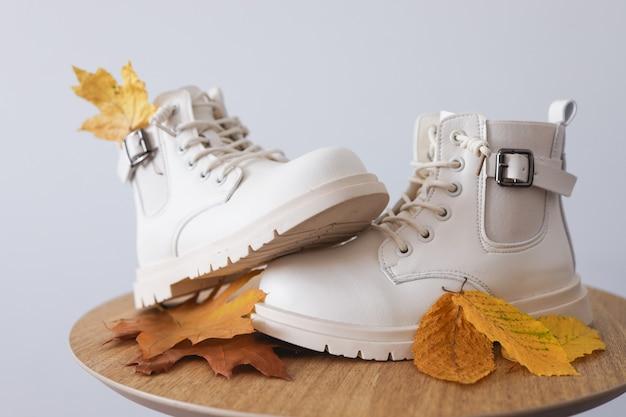 Mooie herfstschoenen met gele bladeren op een witte achtergrond. plaats voor tekst