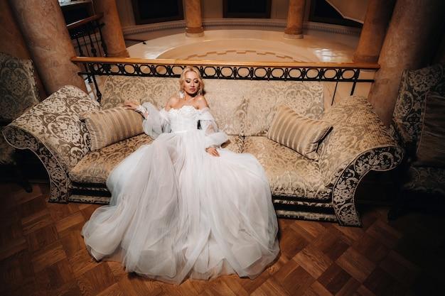 Mooie het huwelijksmake-up van het bruidportret, huwelijkskapsel, huwelijkskleding. schitterende jonge bruid bij binnenland. close-upportret van jonge schitterende bruid. bruiloft. de bruid raakt de oorbellen aan.