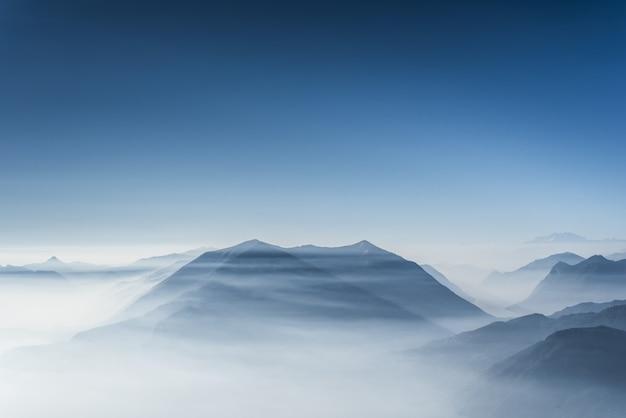 Mooie heuveltoppen bedekt met mist en wolken met heldere blauwe hemel