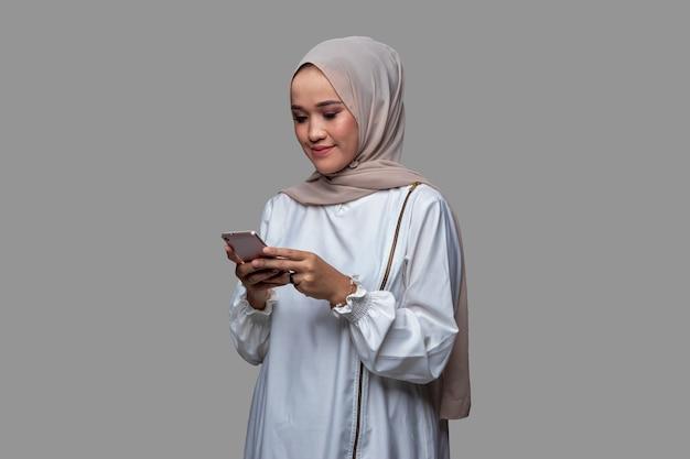 Mooie hijab vrouw is een bericht aan het typen op haar mobiele telefoon met glimlach expressie geïsoleerd op een effen achtergrond