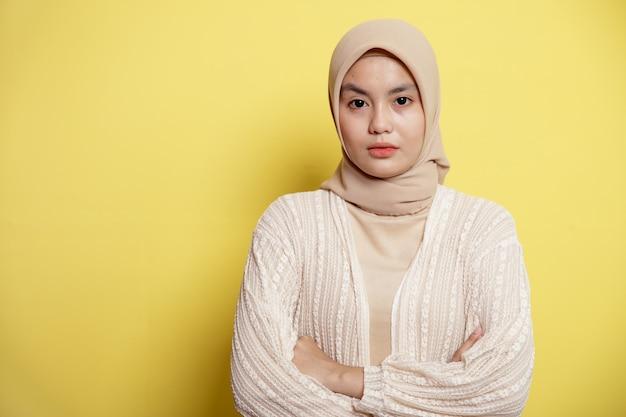Mooie hijab vrouwen gekruiste armen kijken naar de camera geïsoleerd op een gele achtergrond