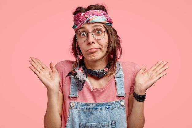 Mooie hippie heeft geen idee van twijfelachtige uitdrukking, spreidt de handpalmen met aarzeling, heeft een onzekere blik