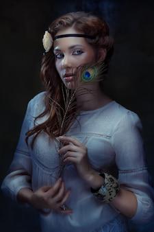 Mooie hippie meisje poseren met een pauwenveer op donkere achtergrond, low key, getinte afbeelding