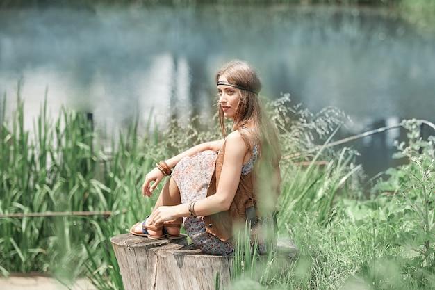 Mooie hippiemeisje, zittend op een boomstronk en kijken naar de vijver. het concept van eenheid met de natuur