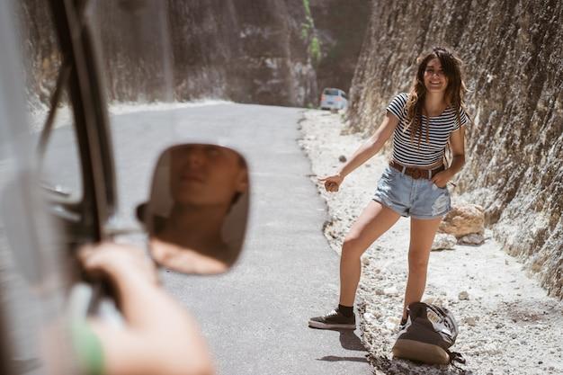 Mooie hippievrouw die zich op een weg met duim bevindt