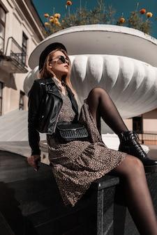 Mooie hipster jonge vrouw model met zonnebril in mode kleding met stijlvolle vintage jurk met leren jas en handtas zit in de stad op een zonnige dag