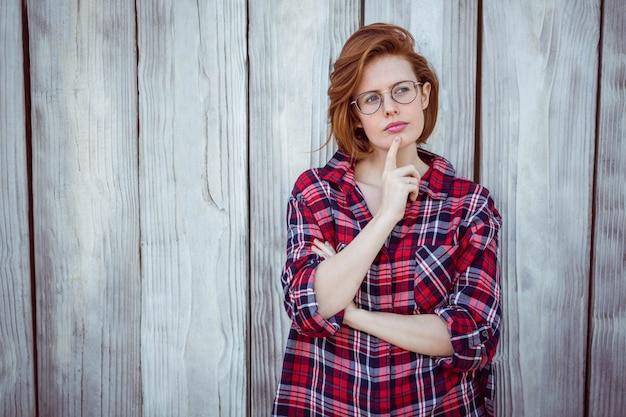 Mooie hipster vrouw denken, met haar vinger op haar gezicht,