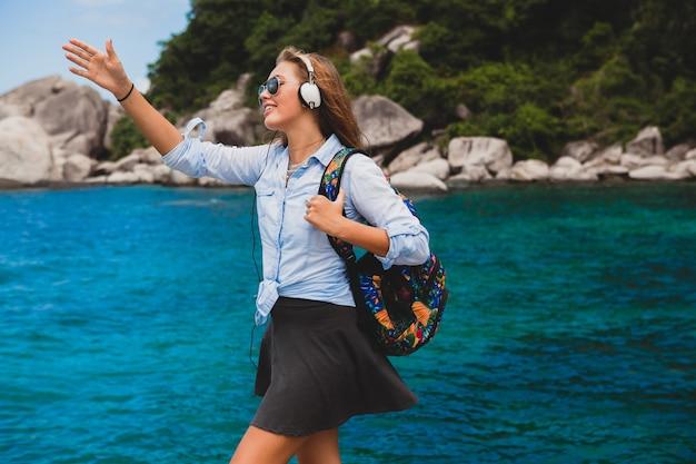 Mooie hipster vrouw reist de wereld rond met rugzak, glimlachend, gelukkig, positief, luisteren muziek in koptelefoon, blauwe tropische oceaan achtergrond, zonnebril, sexy, zomervakantie,