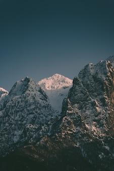 Mooie hoge rotsachtige bergen met daartussen een besneeuwde berg