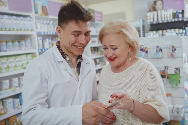 Mooie hogere vrouw die bij drogisterij winkelt