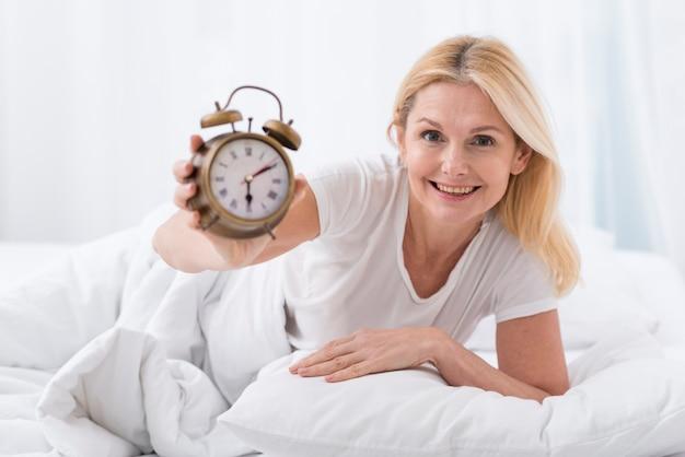 Mooie hogere vrouw die een klok houdt