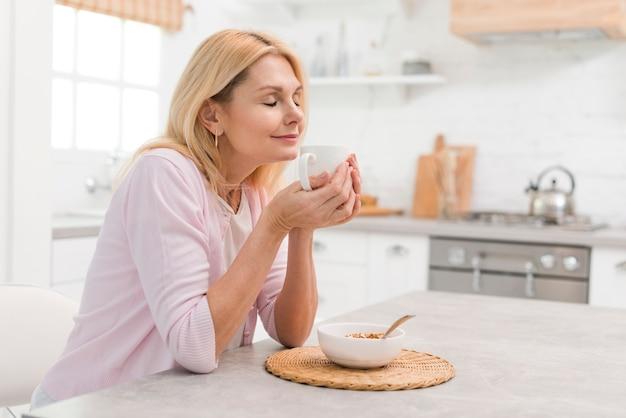 Mooie hogere vrouw die van ontbijt geniet