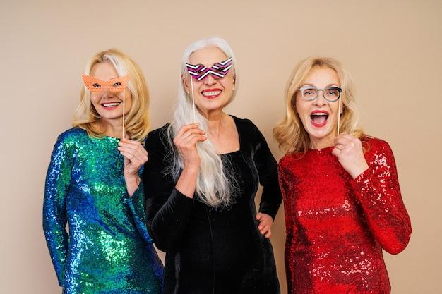 Mooie hogere vrouwen met feestelijke elegante kleding die pret hebben op een feestje