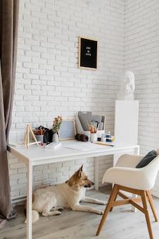 Mooie hond onder kunstenaarsbureau
