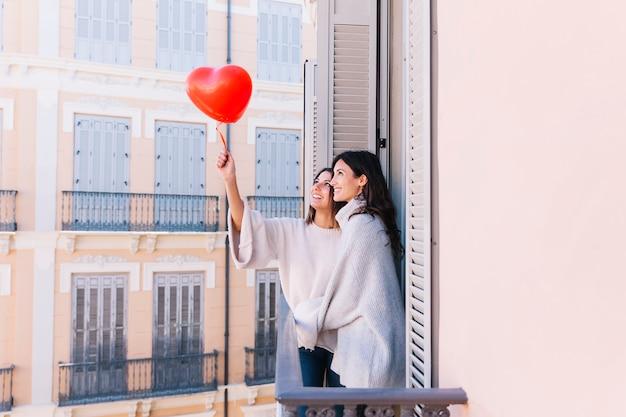 Mooie houdende van vrouwen met ballon op terras