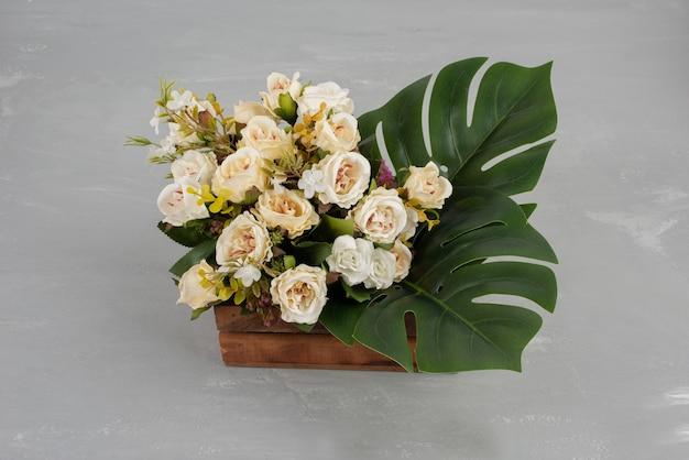 Mooie houten kist met witte rozen op grijze tafel.