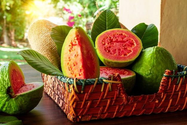 Mooie houten mand met rode guave en wat groene bladeren bij zonsondergang