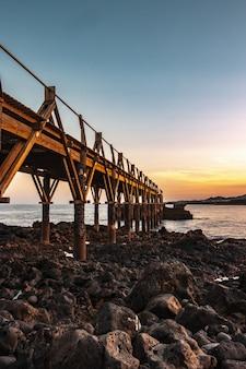 Mooie houten pier aan de kust van de zee met een prachtige zonsondergang