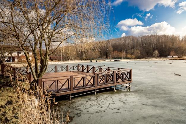 Mooie houten pier op meer bedekt met ijs op zonnige dag