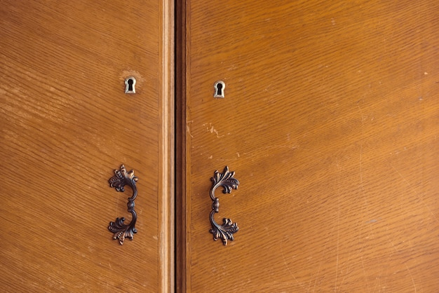 Mooie houten retro kast gesloten op sleutel. mooie deuren van kast met sleutelgat en vintage deurklink van messing close-up. achtergrondafbeelding van grunge houten deuren van kast.