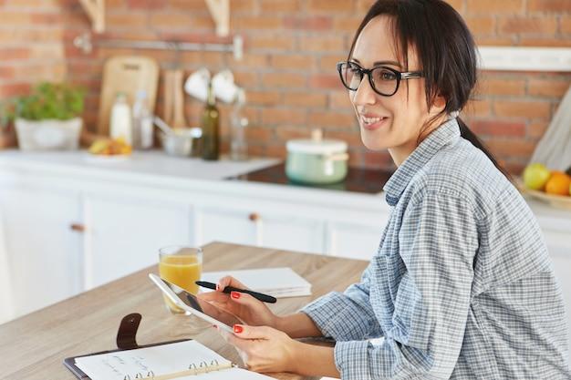 Mooie huisvrouw die alleen is in de keuken, houdt moderne tablet vast,