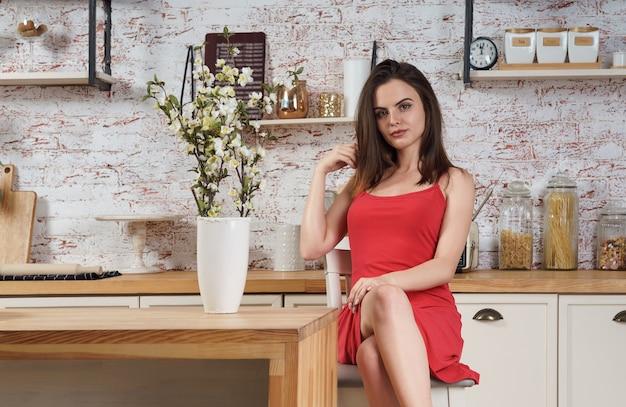 Mooie huisvrouw die jurk draagt en in de keuken zit