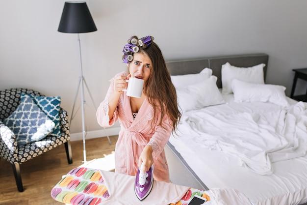 Mooie huisvrouw in roze badjas met krultang thuis bij het strijken van kleren. ze drinkt thee en ziet er moe uit.