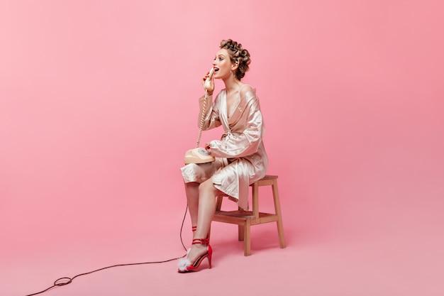 Mooie huisvrouw in roze gewaad emotioneel praten over de telefoon op geïsoleerde muur